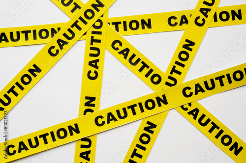 Fotografia  Yellow Caution tapes crossing on white background