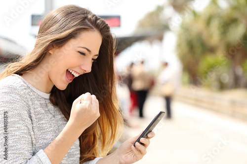 Euphoric woman watching her smart phone in a train station Fototapet