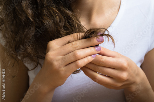 Fototapeta  Female hand of a young girl holding the ends of her curly hair