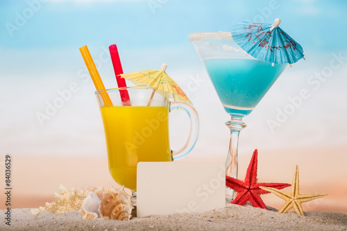 Foto Coctails and blank paper in the sand