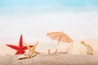Umbrella, shells and starfishes in sand