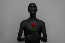 A Man With Black Skin Holding A Red Rose, Black Death Isolated
