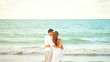 A young couple hold each other and look out to the water at the beach
