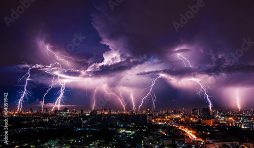 Montage in der Fensternische Onweer Lightning storm over city in purple light