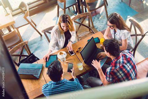 Fotografía  Grupo de jóvenes sentados en un café