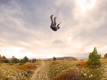 Man Falling Down From The Sky In Autumnal Landscape