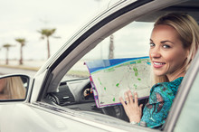 Pretty Young Woman Sitting In Car With A Roads Map