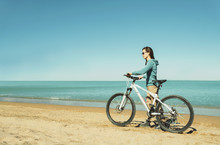Girl Walking With A Bicycle On Beach