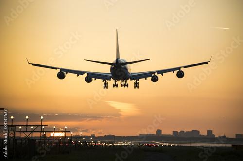 Obraz Plane landing when sunrise started. - fototapety do salonu