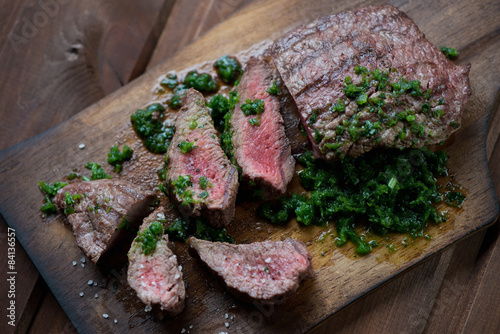 Sliced beef barbecue steak with chimichurri sauce, studio shot Poster