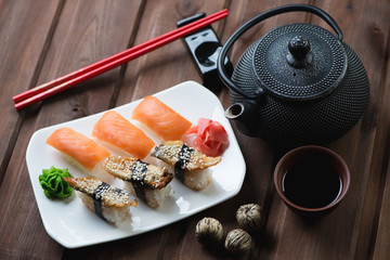 Fototapeta Do sushi baru Sushi set with chopsticks and tea over dark wooden background