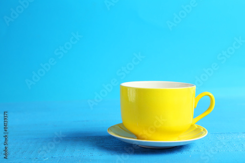 Fototapeta Yellow cup on blue wooden background obraz na płótnie