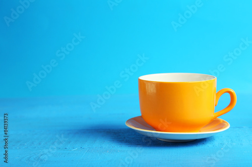 Fototapeta Orange cup on blue wooden background obraz na płótnie