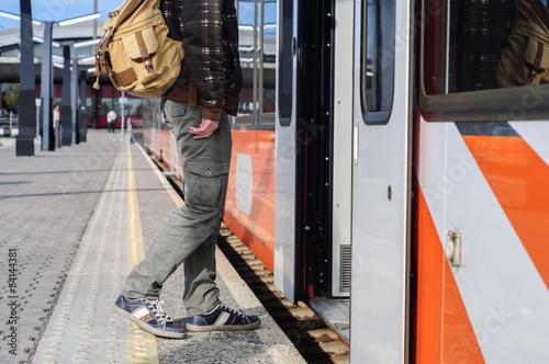 Young tourist man on railway station near train doors