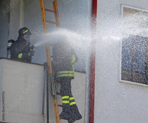 Firefighter sprays water with the spear fighting - Buy this