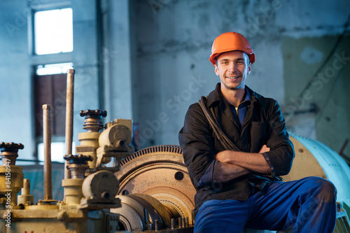 Portrait worker in helmet near the turbine. Work the factory