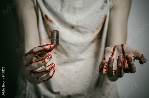 Fotografía a man holding a bloody razor for suicide in the studio