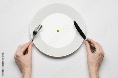 Valokuva  hands holding knife and fork on a plate with green peas