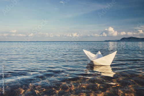 Fotografia  origami paper sailboat sailing on blue water
