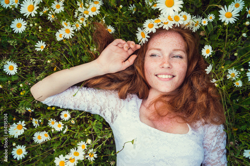 Fényképezés  Beautiful young girl with curly red hair in camomile field