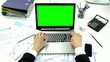 Man hand on laptop keyboard with green screen monitor in the