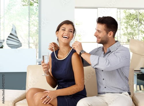 Photo Happy woman with champagne getting pearl necklace