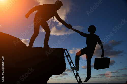 Fotografía  Teamwork of two men hiker helping each other on top of mountain climbing team, beautiful sunset landscape