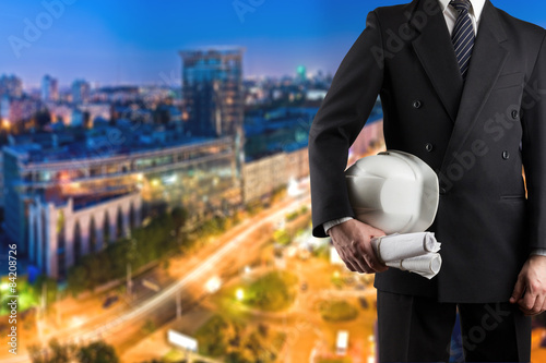 Poster Industrial geb. Architect hand holding white safety helmet for workers security and blueprints standing in front of blurred urban background
