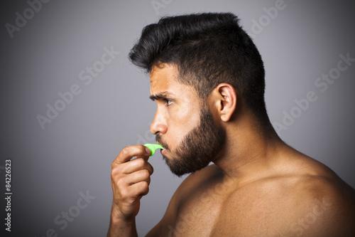 Fényképezés  Joven latino con barba soplando pito