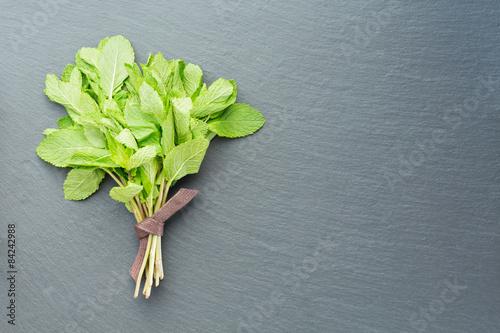 Staande foto Lelietje van dalen Fresh mint on a dark stone background