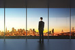 Businessman in empty office looking at beautiful skyline