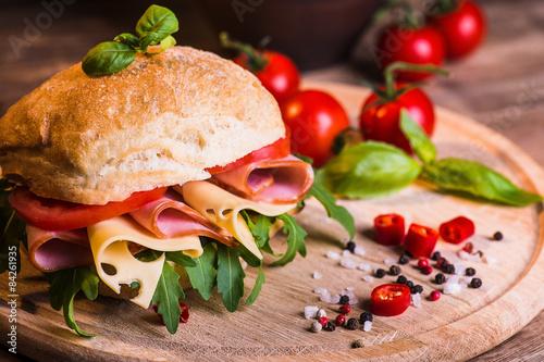 Valokuva  Italian ciabatta with ham and cheese on the wooden background