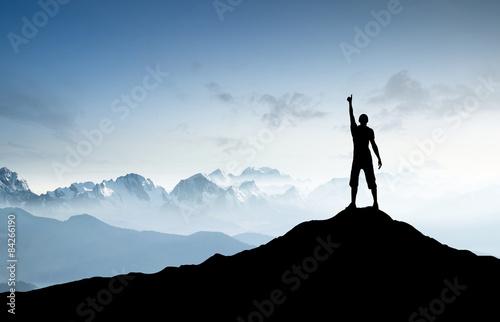 Winner silhouette on the mountain peak