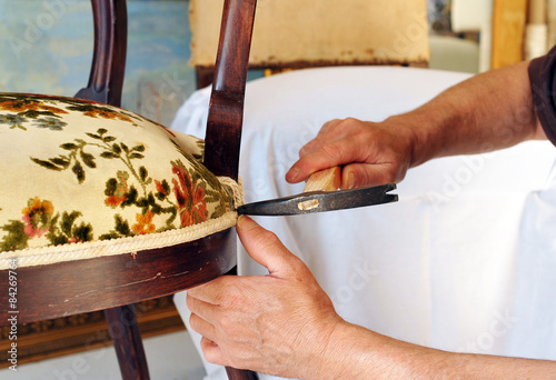 Photo Upholsterer lining the seat of a chair