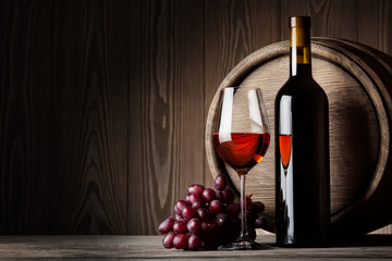 Fototapeta Do winiarni Black bottle and glass of red wine with grapes and barrel