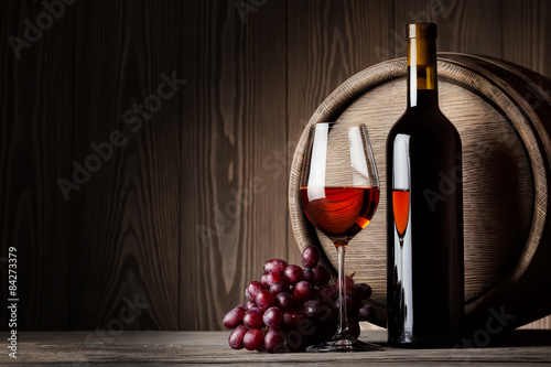 Black bottle and glass of red wine with grapes and barrel