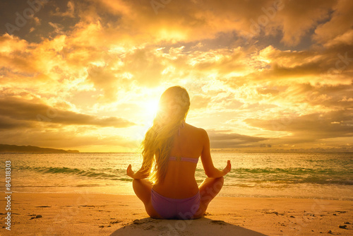 Fényképezés  Young woman relaxing in lotus position during a beautiful sunset