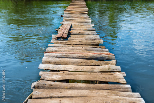 Old wooden bridge through the river Canvas