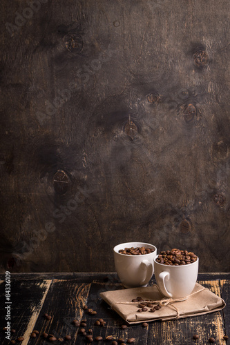 Poster Café en grains Cup with coffee beans at dark wooden background