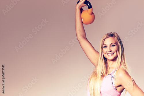 Valokuva  Woman smiling at camera and lifting kettlebell.