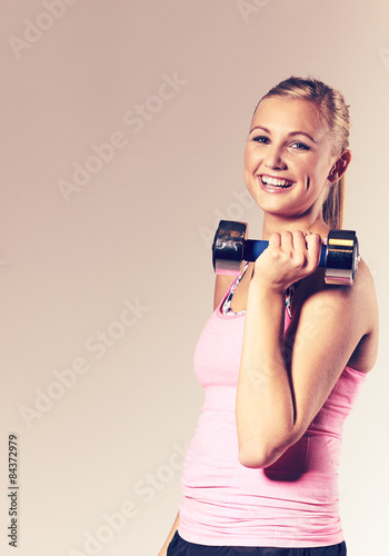 Valokuva  Woman smiling and holding a free weight.