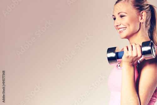 Valokuva  Woman smiling and holding dumbbell