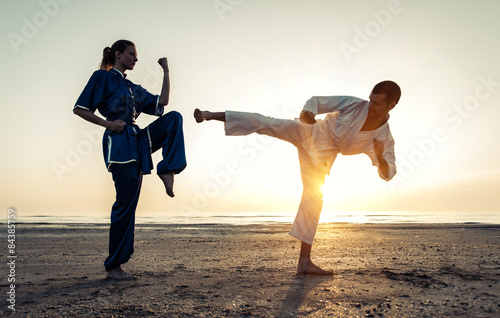 Tuinposter Vechtsport couple training in martial arts on the beach