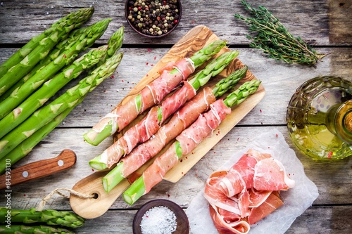 Fotografía Fresh organic asparagus wrapped in Parma ham on a cutting board