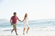 Young Couple Running Along Sandy Beach On Holiday