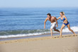 Young Couple Running Along Summer Beach