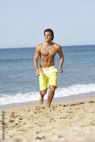 563a3769ca Young Man Wearing Swimming Costume Running Along Beach - Buy this ...