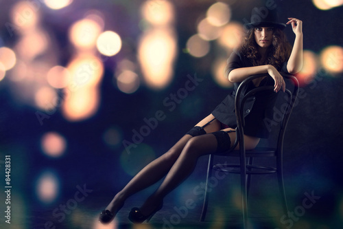 Carta da parati Sexy young woman sitting on a chair against a background of bright lights at night