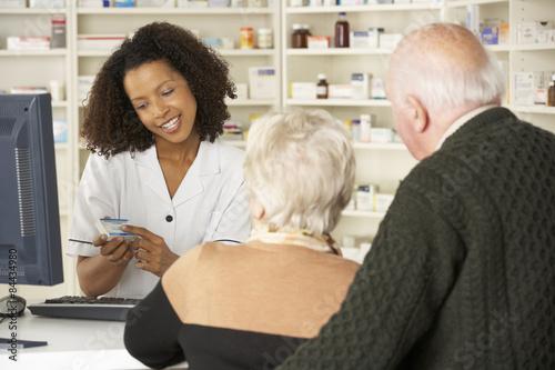 Ingelijste posters Apotheek Pharmacist in pharmacy with senior couple