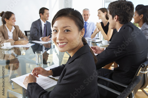 Fototapety, obrazy: Asian Businesswoman Sitting Around Boardroom Table With Colleagues